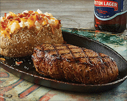plate of steak and baked potato with bottle of beer